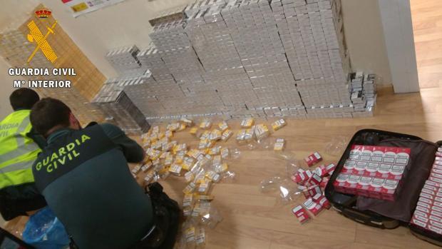 Los agentes abren las maletas con cajetillas de tabaco que transportaban en un coche desde Lisboa