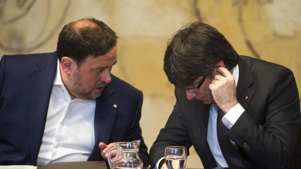 El presidente, de la Generalitat, Puigdemont, y el vicepresidente, Junqueras, durante una reunión del Ejecutivo
