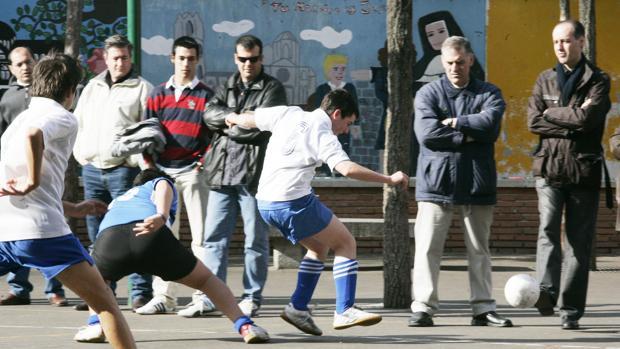 Un grupo de chavales, jugando al fútbol ante la mirada de varios espectadores