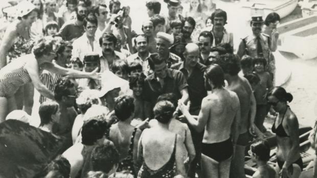Adolfo Suárez recibe el saludo de un grupo de veraneantes en la playa de Bagur (Gerona)