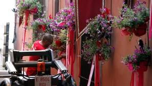 Un operario coloca las flores en las fachadas del recorrido procesional