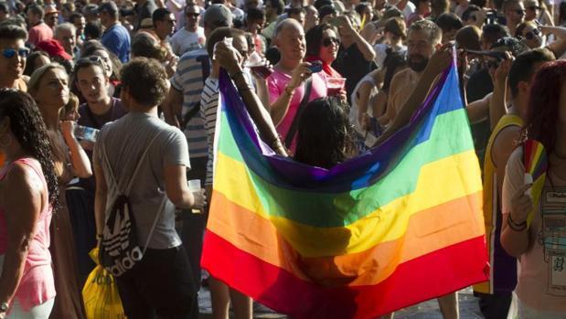 Una mujer sosiene una bandera arcoíris durante las fiestas del Orgullo Gay