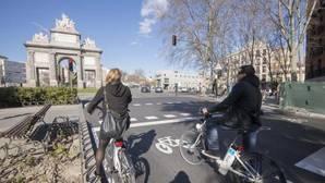 Dos ciclistas esperan en un semáforo de la capital