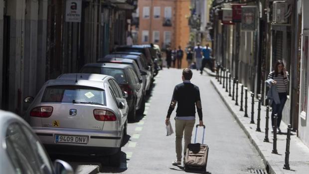Un joven pasea por una calle de Lavapiés, epicentro de las viviendas de uso turístico de Madrid