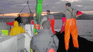 Pescadores, al amanecer, en un barco cerquero