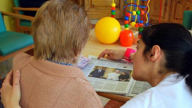 Una cuidadora ayuda a leer el periódico a una mujer dependiente
