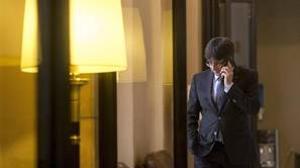 El presidente de la Generalitat, Carles Puigdemont, habla por teléfono en los pasillos del parlamento de Cataluña