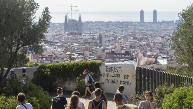 Turistas pasean por los alrededores del Parque Guell de Barcelona, donde han aparecido pintadas contra el turismo
