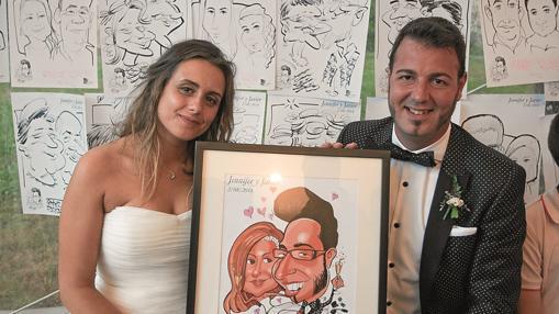Una pareja muestra su caricatura delante de un mural con los retratos de los invitados