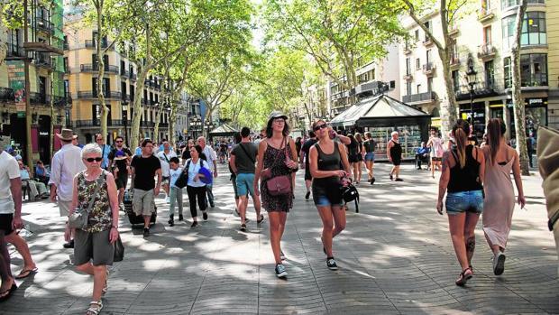 Turistas y barceloneses paseando ayer por las Ramblas
