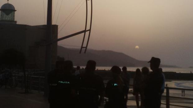 Agentes de Policía, este lunes, cuando se producía el eclipse en Las Canteras, Gran Canaria, afectada de calima