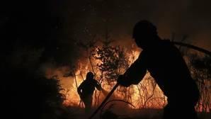 Dos brigadistas trabajan en la extinción de un fuego en Santiago esta semana