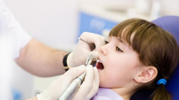 Un dentista revisa la boca a una niña, en imagen de archivo