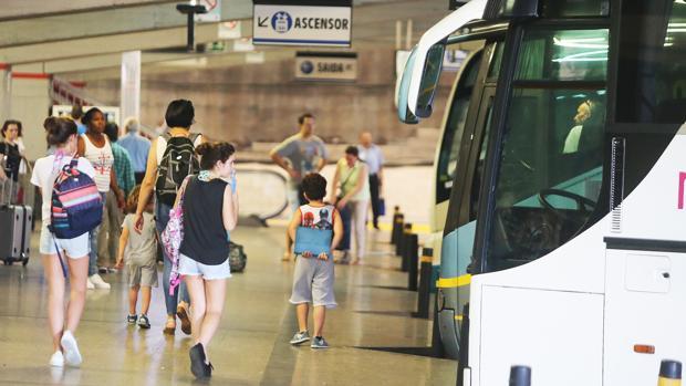 Viajeros adultos y menores, en la estación de autobuses de Santiago