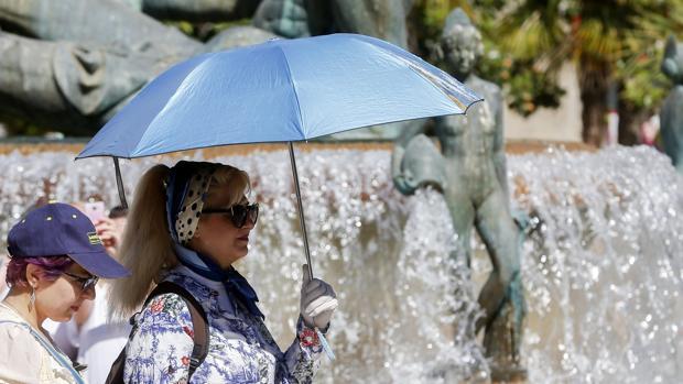 Imagen de una mujer protegiéndose del calor tomada este jueves en el centro de Valencia