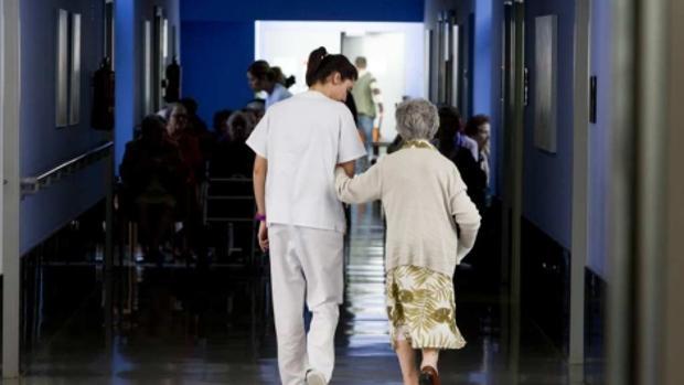 Una anciana paseando por una residencia de mayores