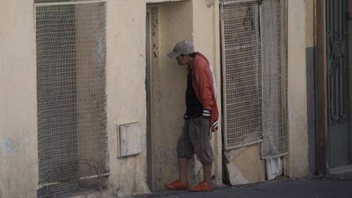 Un hombre de origen asiático espera para entrar en un bloque «okupado»