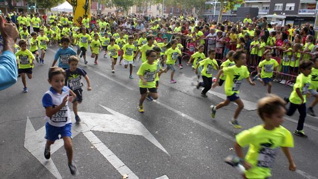 Decenas de niños toledanos corren tras salir de la meta en la calle Méjico