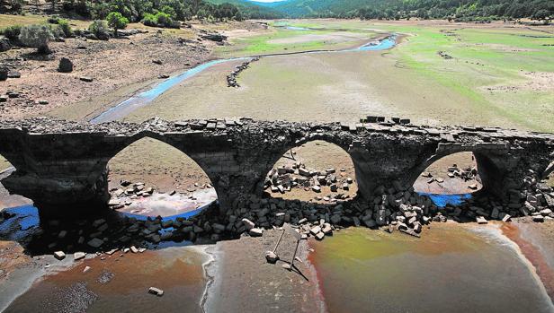 El puente romano, normalmente cubierto por el agua, se ve al haber bajado mucho el nivel en el embalse de Cuerda del Pozo