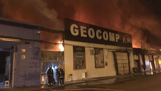 Los bomberos tratan de apagar las llamas, en el polígono de Cobo Calleja