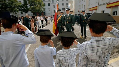 Cuatro niños saludan el paso de los guadias civiles hoy en Comandancia de València durante los actos de la Virgen del Pilar, patrona del cuerpo