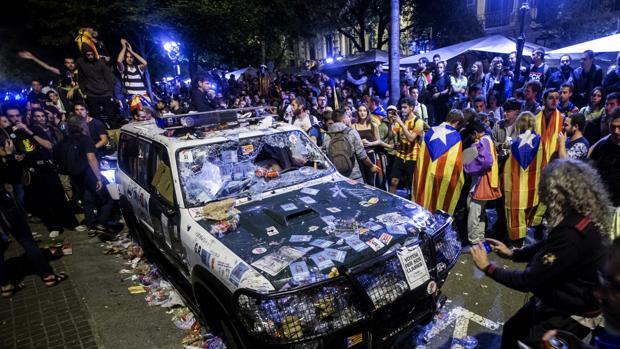 Un vehículo de la Guardia Civil, destrozado por los manifestantes, en Barcelona