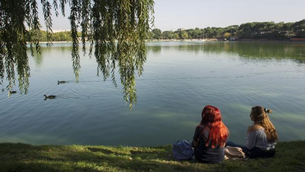 Dos jóvenes se sientan sobre la zona del lago de la Casa de Campo que se convertirá en una «playa»