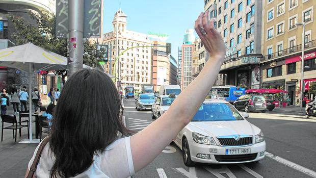Una usuaria para un taxi en Gran Vía