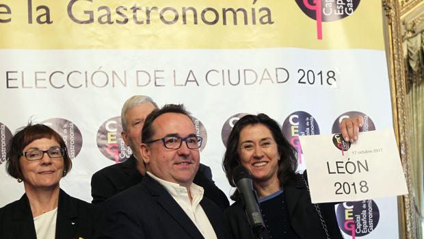 La presidenta de Paradores, Maria Ángeles Alarcó, enseña el cartel con el nombre de la ciudad elegída como capital española de la gastronomía 2018