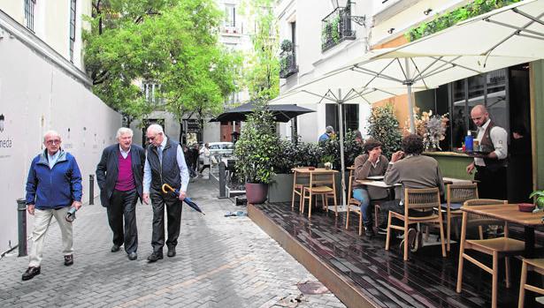 Tres hombres pasean junto a uno de los locales que se encuentra en el callejón de Puigcerdá
