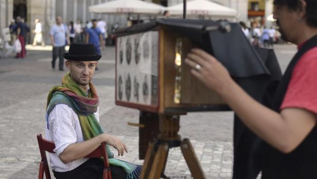Un fotógrafo «minutero» retrata a un cliente en la Plaza Mayor
