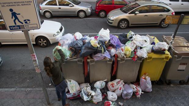 Una mujer tira la basura en un contenedor abarrotado de basura