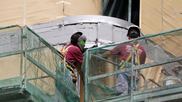 Dos obreros trabajan en la rehabilitación de una fachada