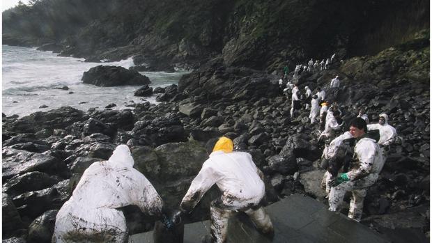 Voluntarios limpiando en la cala de Corveiro en Fisterra en 2002