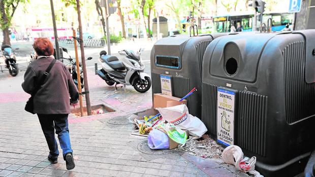 Una mujer camina delante de un contenedor con residuos en Arganzuela