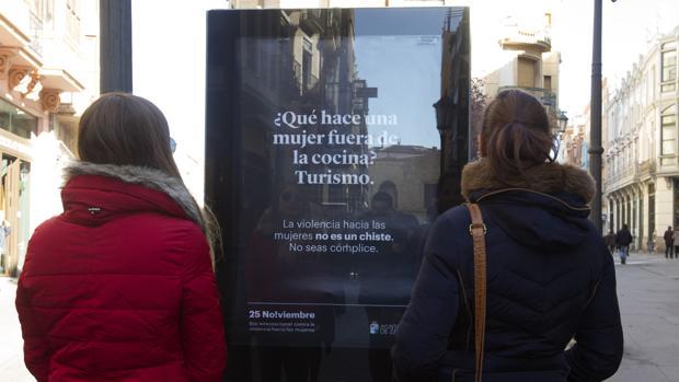 Dos jóvenes contemplan el cartel de la polémica campaña en las calles de Zamora