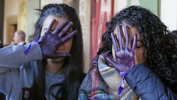 Dos jóvenes muestran sus manos teñidas de violeta en repulsa de la violencia machista