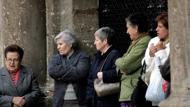 Varias mujeres de protegen del frío en el centro de Valencia