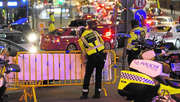 Un policía municipal coloca una valla durante el corte de tráfico