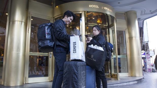 Una pareja de turistas asiáticos en la puerta del hotel Emperador