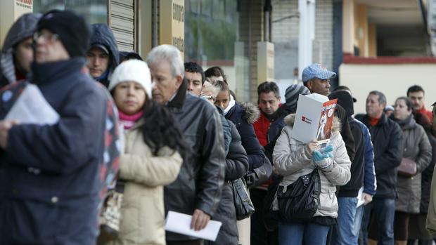 Gente haciendo cola para entrar en una oficina de empleo en Madrid