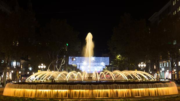 Una fuente iluminada de amarillo en el centro de Barcelona