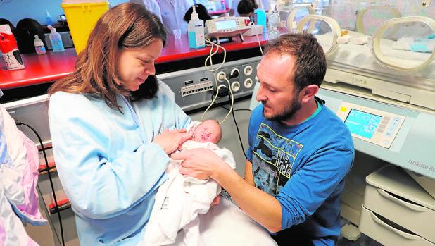 Aura, el primer bebé en nacer en la región en 2018, junto a sus padres en Valladolid