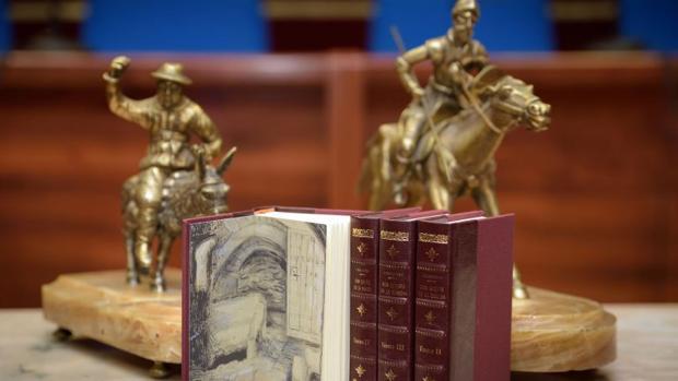 Dos figuras de Sancho Panza y don Quijote, detras de una edición del libro