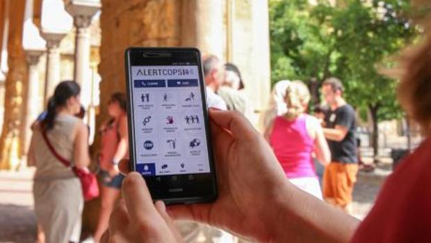 Una ciudadana muestra la aplicación «Alertcops» en su teléfono