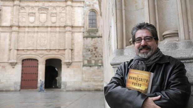Luis García Jambrina, con su nuevo libro, junto a la fachada de la Universidad de Salamanca