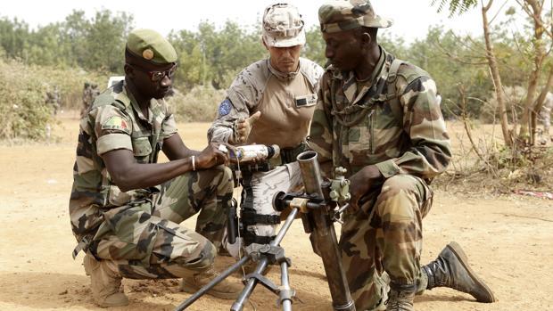 Un militar español instruye a dos cadetes en mortero