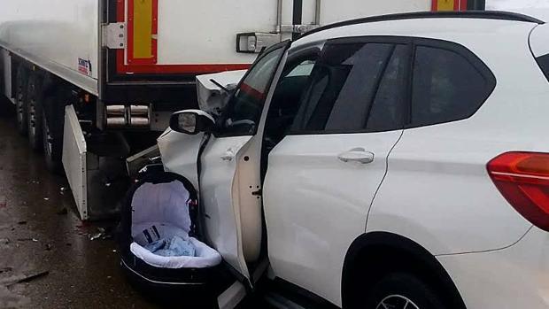 El capazo en el que iba el bebé fallecido, junto al coche en el que también murió su madre