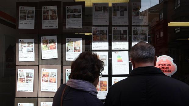 Una pareja mira los anuncios de una inmobiliaria en Valladolid