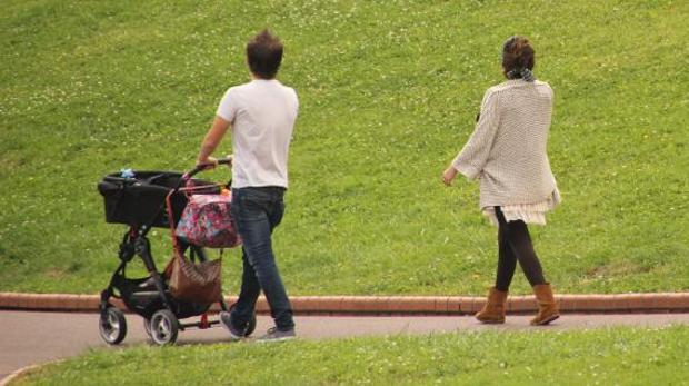 Una pareja pasea un bebé en el carrito